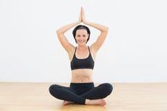 Smiling woman sitting in lotus pose at fitness studio Royalty Free Stock Image