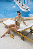 Smiling woman sitting on lounge chair at poolside royalty free stock image