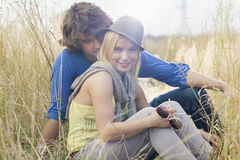 Smiling woman sitting with loving man in field Royalty Free Stock Images