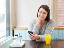 Smiling woman sitting at with mobile phone Stock Image
