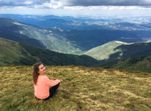 Smiling woman sitting on mountain top. Smiling woman sitting on the mountain top enjoying the view Royalty Free Stock Photography