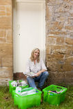 Smiling woman sitting near bins full of recycling materials Stock Photography
