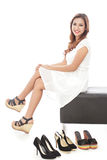 Smiling woman sitting next to pairs of shoes. Full body portrait of smiling woman sitting next to pairs of shoes isolated on white background Royalty Free Stock Photos