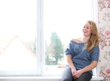 Smiling woman sitting next to window Royalty Free Stock Images