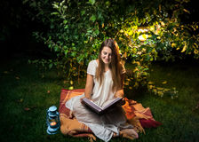Smiling woman sitting at night in garden and reading big old boo Stock Image