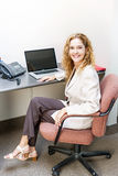 Smiling woman sitting at office desk Royalty Free Stock Photos