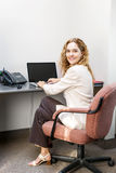 Smiling woman sitting at office desk Royalty Free Stock Images