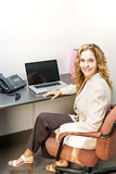 Smiling woman sitting at office desk Stock Photo