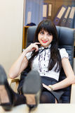 Smiling woman sitting in an office at a desk Stock Photo