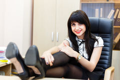 Smiling woman sitting in an office at a desk Royalty Free Stock Photos