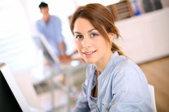 Smiling woman sitting in office Stock Photo