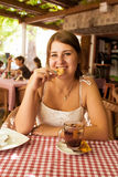 Smiling woman sitting at outdoor cafe and eating cookie Royalty Free Stock Photos