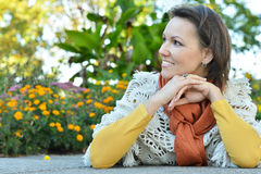 Smiling woman sitting outdoors in autumn Royalty Free Stock Image