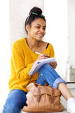 Smiling woman sitting outdoors and writing book Royalty Free Stock Photo