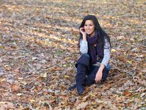 Smiling Woman Sitting Outside in Autumn Leaves Royalty Free Stock Photos