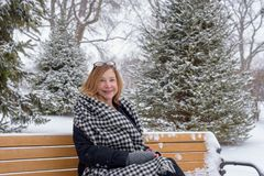 Smiling woman sitting on park bench in chicago with snow falling. Happy person sitting on park bench in winter with snow falling Stock Photo