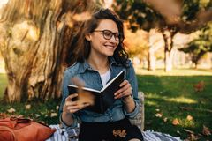 Smiling woman sitting at park with book and leaves falling aroun stock image