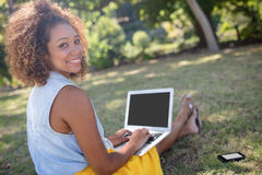 Smiling woman sitting in park and using laptop Stock Image