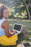Smiling woman sitting in park and using laptop. Portrait of smiling woman sitting in park and using laptop on a sunny day Royalty Free Stock Photography