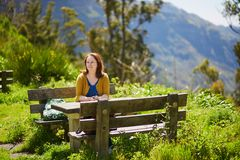 Smiling woman sitting at the picnic table Stock Image