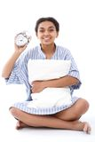Smiling woman sitting with pillow and alarm clock Stock Photo