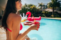 Beautiful woman enjoying a day at the poolside. Smiling woman sitting by the pool having a cocktail. Beautiful female enjoying a summer day at the poolside Stock Photo