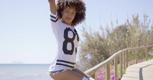 Smiling woman sitting on railings. Young woman in shirt and shorts sitting on railings of sidewalk on beach and looking at camera stock footage