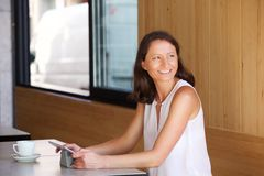 Smiling woman sitting at restaurant with tablet Royalty Free Stock Photos