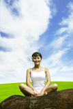 Smiling woman sitting on the rock Royalty Free Stock Photo