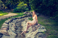 Smiling woman sitting on rock by stream in park Royalty Free Stock Photo