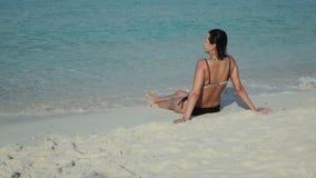 Smiling woman sitting on sandy sea beach stock video