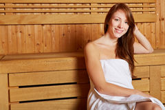 Smiling woman sitting in a sauna Stock Photos