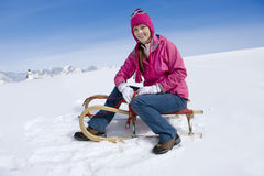 Smiling woman sitting on sled on snowy ski slope Stock Images