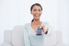 Smiling woman sitting on sofa changing tv channel Royalty Free Stock Photos