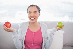 Smiling woman sitting on sofa holding green and red apple Royalty Free Stock Photos