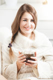 Smiling woman sitting on sofa and holding tea cup Royalty Free Stock Image