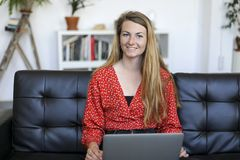 Smiling woman sitting on a sofa at home using a laptop stock photography