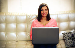 Smiling woman sitting on the sofa with laptop Royalty Free Stock Photography