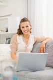 Smiling woman sitting on sofa in living room with laptop Royalty Free Stock Images