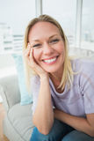 Smiling woman sitting on sofa in living room Stock Images
