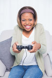 Smiling woman sitting on sofa playing video games Royalty Free Stock Images