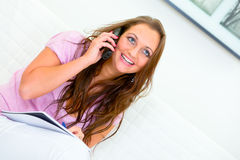 Smiling woman sitting on sofa and talking on phone Royalty Free Stock Images