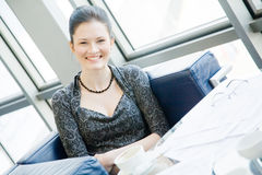 Smiling woman sitting at the table Stock Images