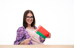 Smiling woman sitting at the table with Belarusian flag Royalty Free Stock Photo