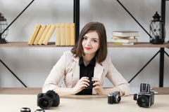 Smiling woman sitting at table with cameras Royalty Free Stock Photos