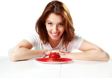Smiling woman sitting on the table with fresh strawberry cake Stock Photos