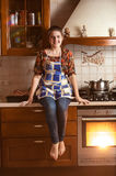 Smiling woman sitting on tabletop while baking in oven Stock Photography