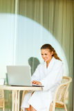 Smiling woman sitting on terrace and using laptop Stock Images