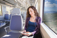 Smiling woman sitting in train typing on smartphone Royalty Free Stock Photos