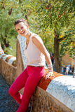 Smiling woman sitting on trencadis style fence in Park Guell. Get inspired by Park Guell in your next trip to Barcelona, Spain. Portrait of smiling young woman Stock Photos